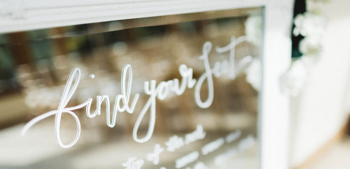 White calligraphy on a silver mirror makes an elegant wedding table plan for a wedding at Gaynes Park