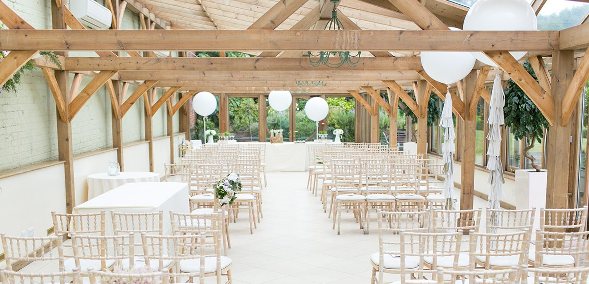 The Orangery at Gaynes Park is decorated with giant white balloons for a fun white wedding ceremony