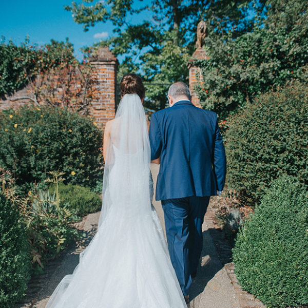 The bride and her father make their way down the Long Walk towards the Orangery at Gaynes Park in Essex