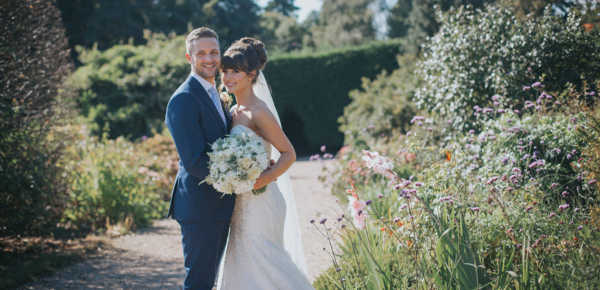 The bride and groom enjoy the gardens at Gaynes Park wedding venue in Essex