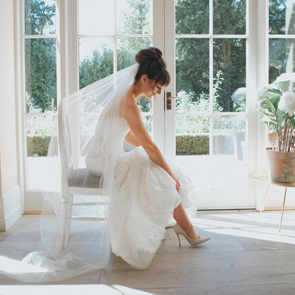 The bride puts on her wedding shoes before her wedding ceremony at Gaynes Park in Essex
