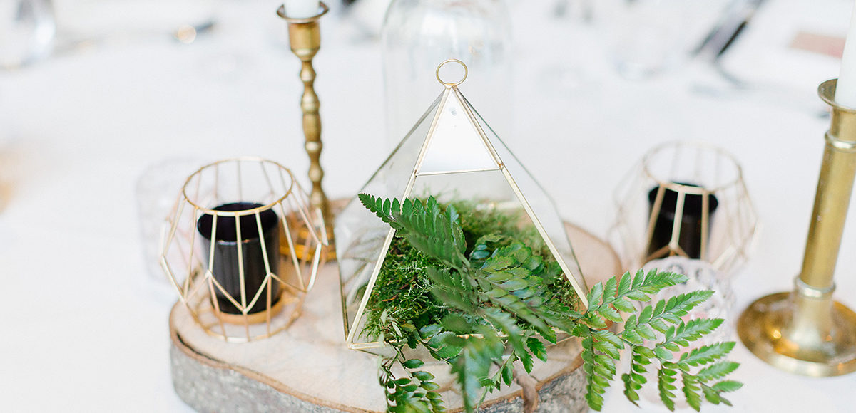 A geometric terrarium is filled with ferns for a modern wedding centrepiece at Gaynes Park