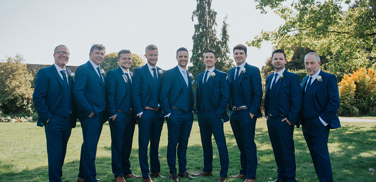 The groom and his groomsmen wear navy wedding suits for a late summer wedding at Gaynes Park