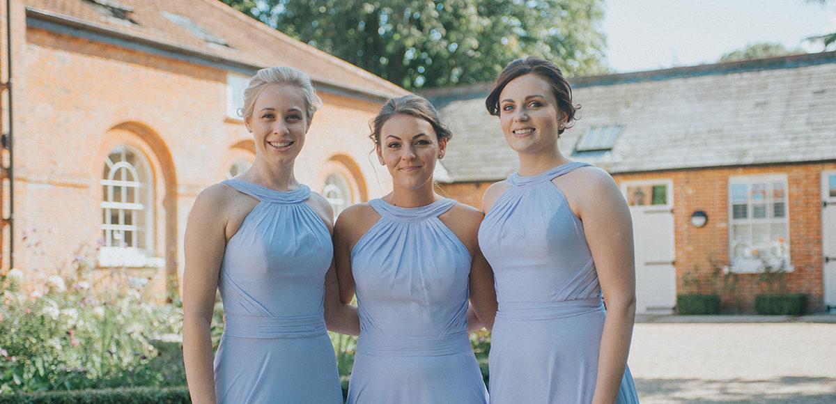 Three bridesmaids wear lilac bridesmaid dresses for a late summer wedding at Gaynes Park
