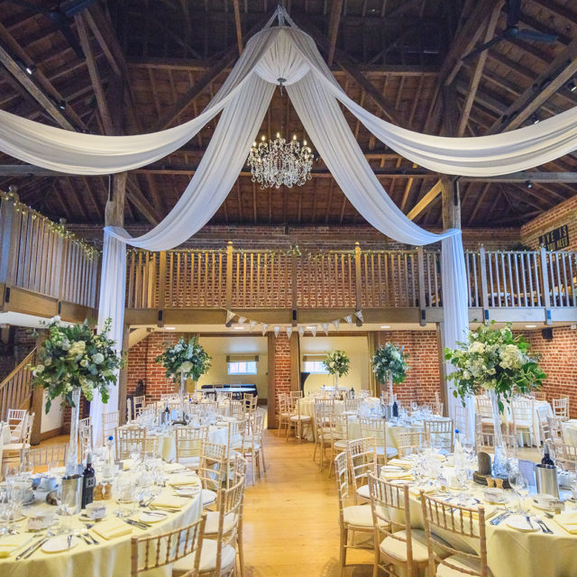 The Mill Barn at Gaynes Park is set up with tall floral wedding centrepieces for a wedding reception