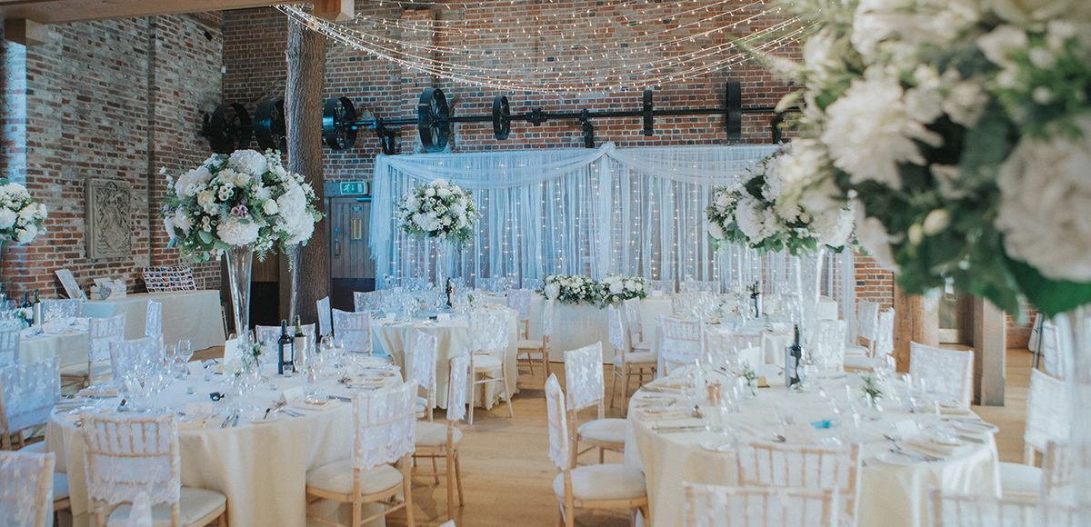 The Mill Barn at Gaynes Park is set up for a glamorous wedding reception