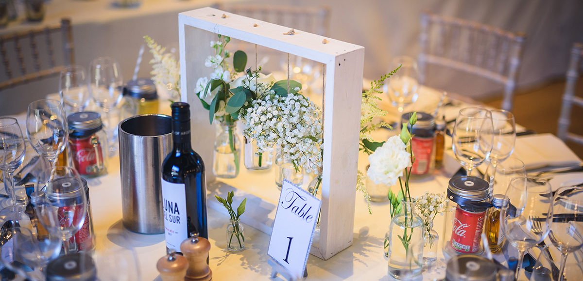 A simple modern table centrepiece works well for a wedding reception in the Mill Barn at Gaynes Park