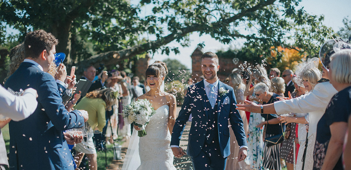 Newlyweds are showered in confetti in the gardens at Gaynes Park following their wedding ceremony