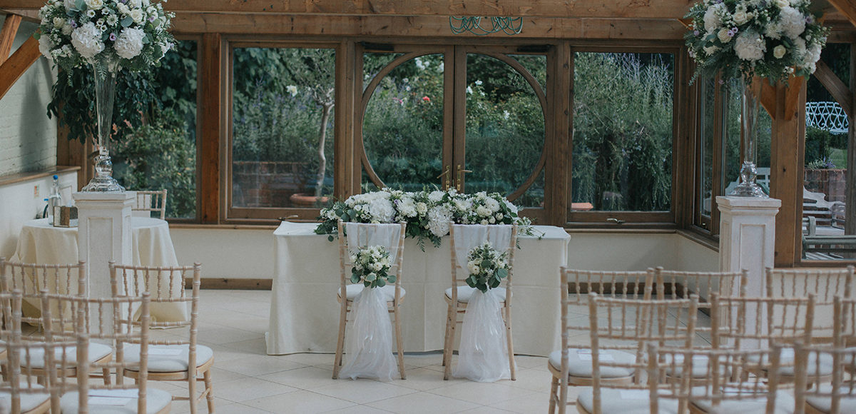 The Orangery at Gaynes Park is dressed in white and greenery florals for a late summer wedding ceremony