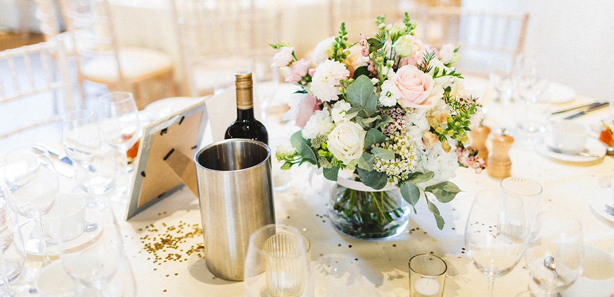 Low pink and cream florals create an elegant wedding table centrepiece at Gaynes Park
