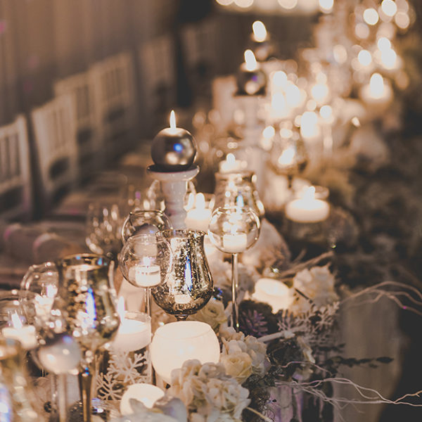 A selection of candles create a romantic wedding centrepiece for a winter wedding at Gaynes Park