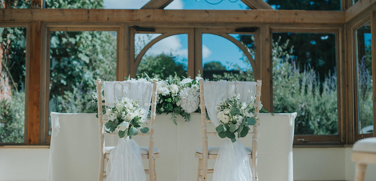 Chairs in the Orangery at Gaynes Park are dressed with white sashes and florals for a wedding ceremony