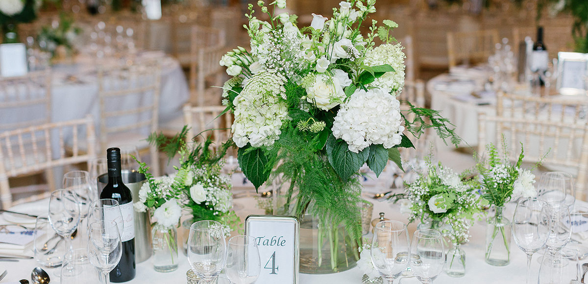 White and greenery filled vases create beautiful country wedding table centrepieces