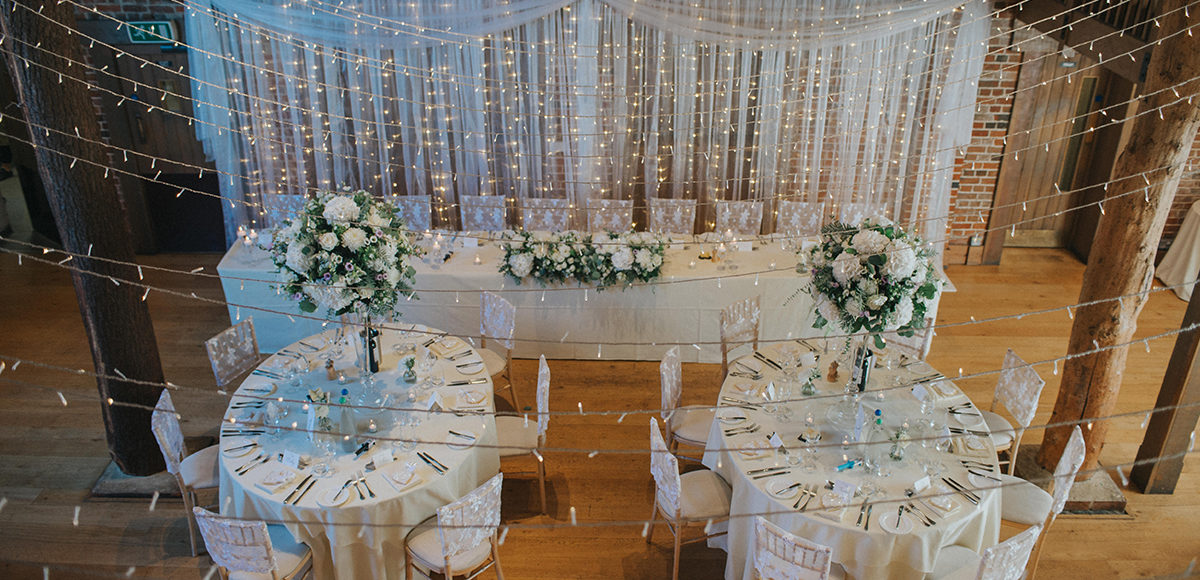 White drapes and florals decorate the Mill Barn at Gaynes Park for a wedding reception
