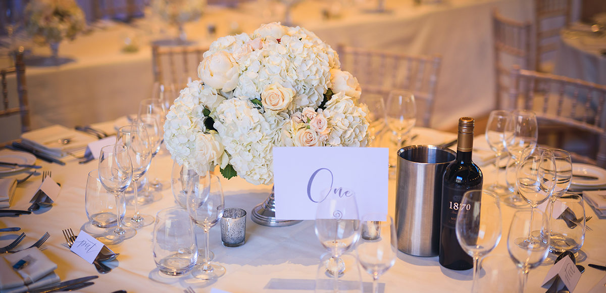 White hydrangeas and roses create an elegant wedding table centrepiece at Gaynes Park