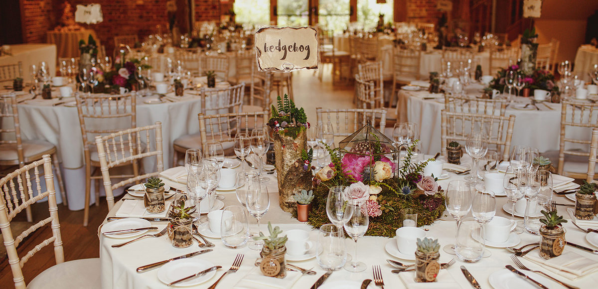 Moss and florals adorned log slices to create whimsical woodland wedding table centrepieces at Gaynes Park